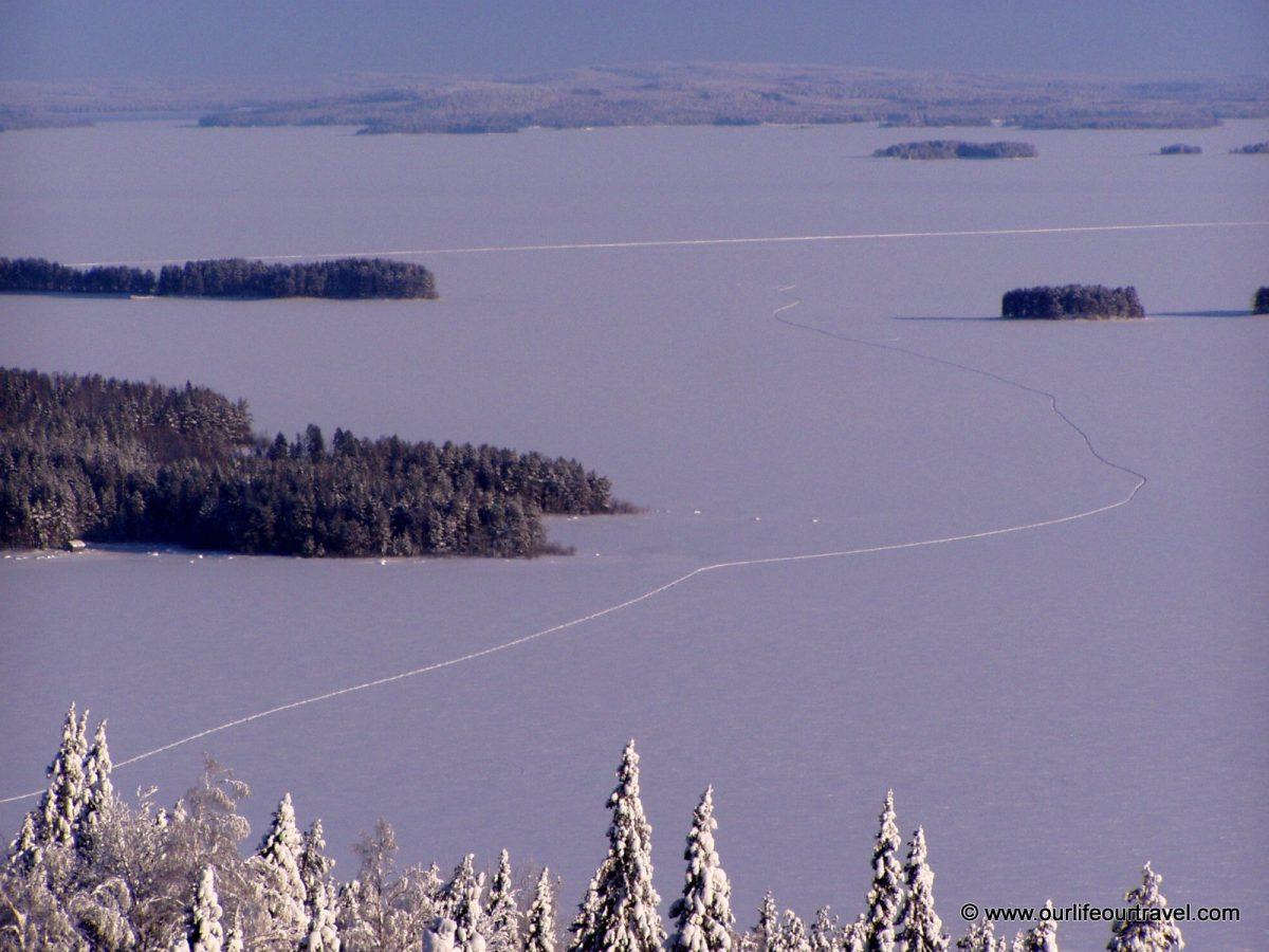 Pielinen-tó: hótalpas szán nyom az előtérben, a Koli-Lieksa főútvonal a háttérben.