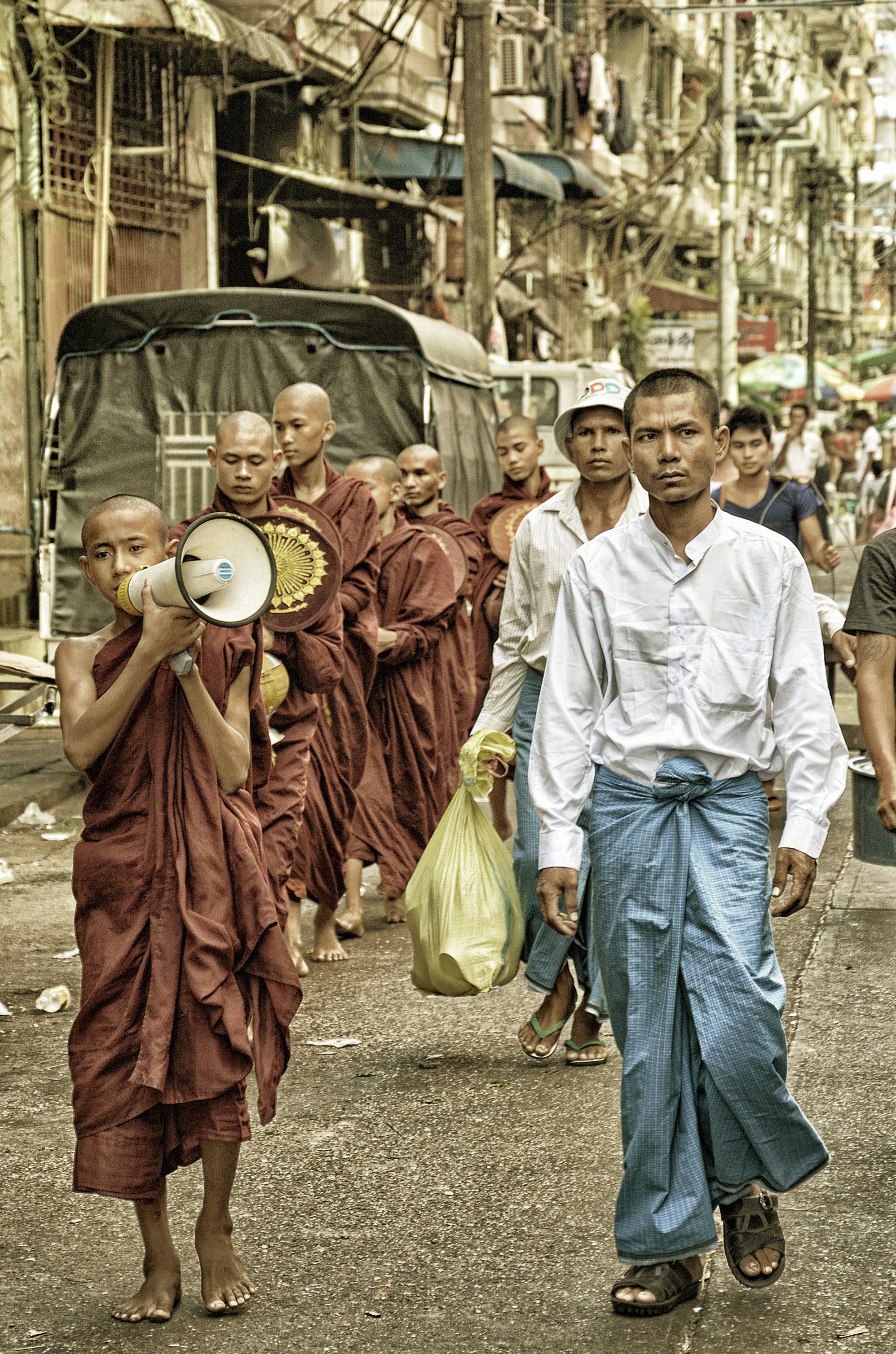 Buddhista szerzetesek adománygyűjtő körúton; jobboldalt burmai férfiak megszokott viseletükben, a derekuk köré tekert szárongban